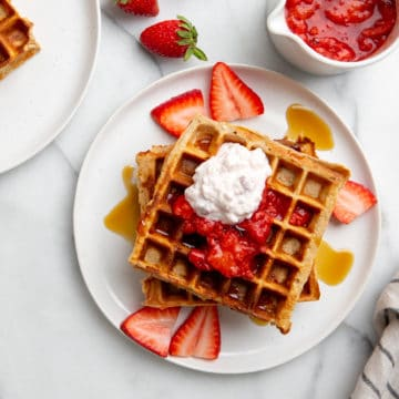 High protein strawberry oat waffles on a plate, topped with strawberries and cottage cheese.