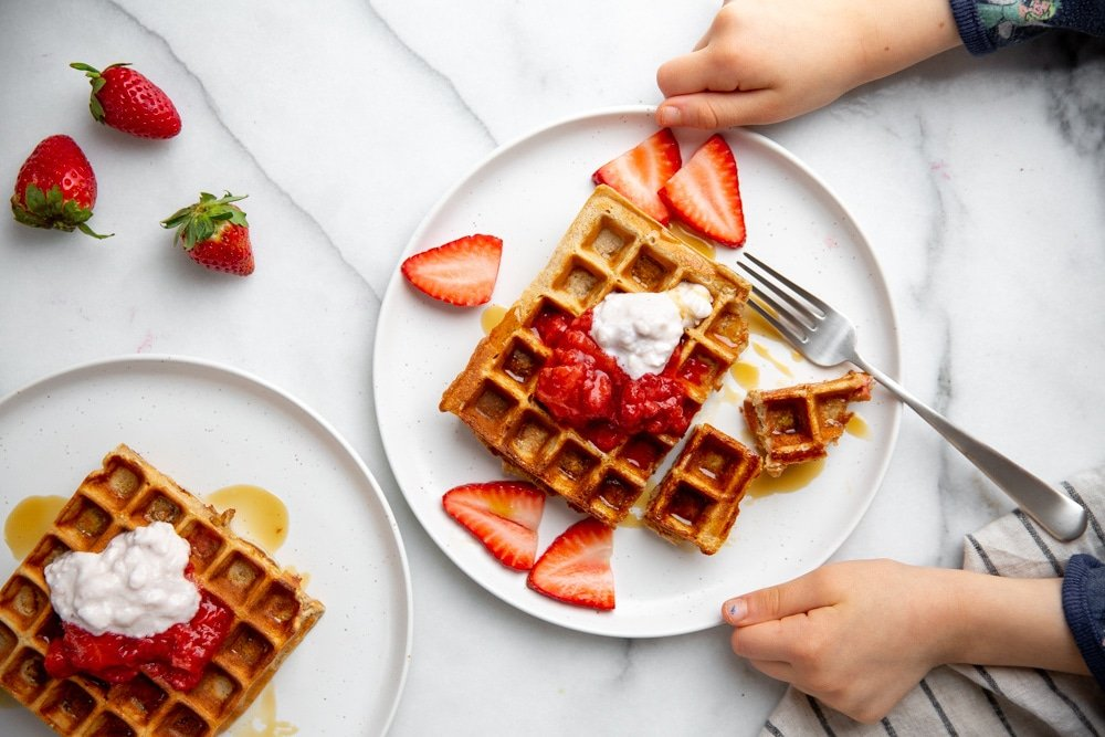 Two child hands grabbing a plate of waffles topped with strawberries and cottage cheese.