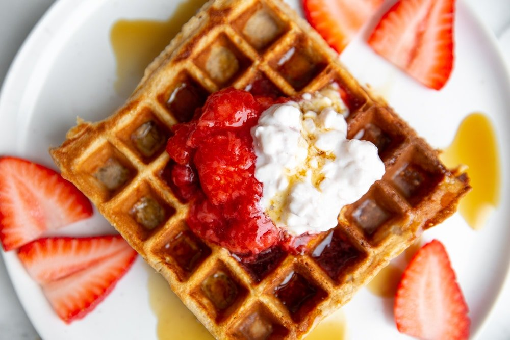 Close up of a high protein cottage cheese waffle topped with strawberry sauce and a dollop of cottage cheese.