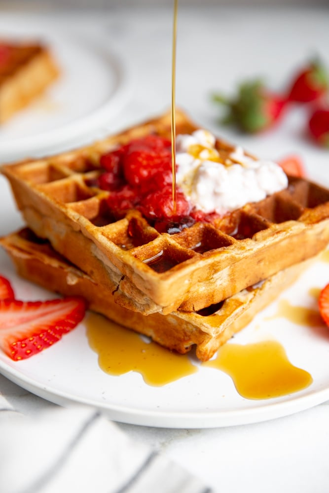Syrup pouring down on two stacked gluten free strawberry oat waffles.