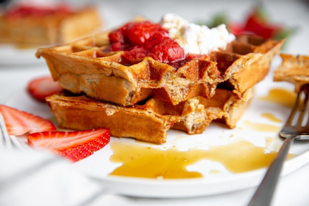 Two stacked cottage cheese waffles with a bite removed, showing the interior of the waffles.