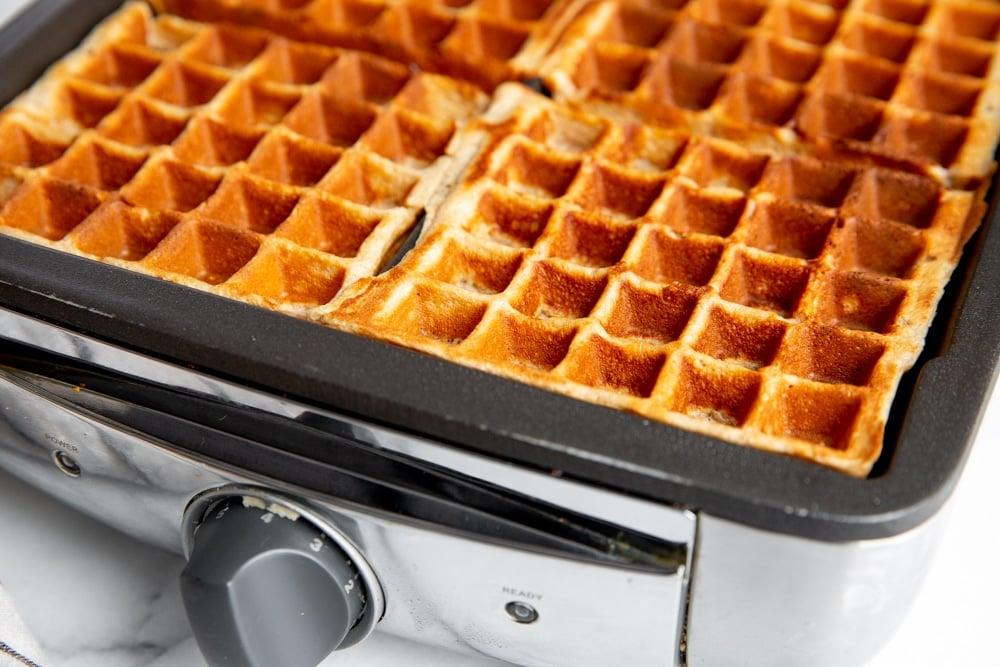 Strawberry oatmeal waffles in a Belgian waffle iron.