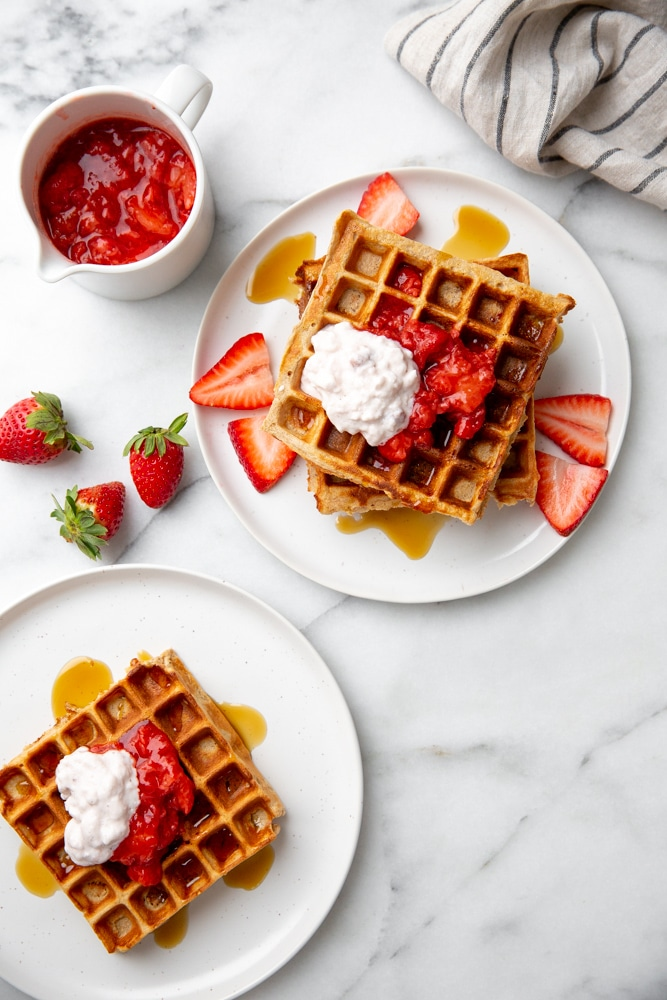 Two plates of strawberry waffles, with a bowl of strawberry sauce alongside.