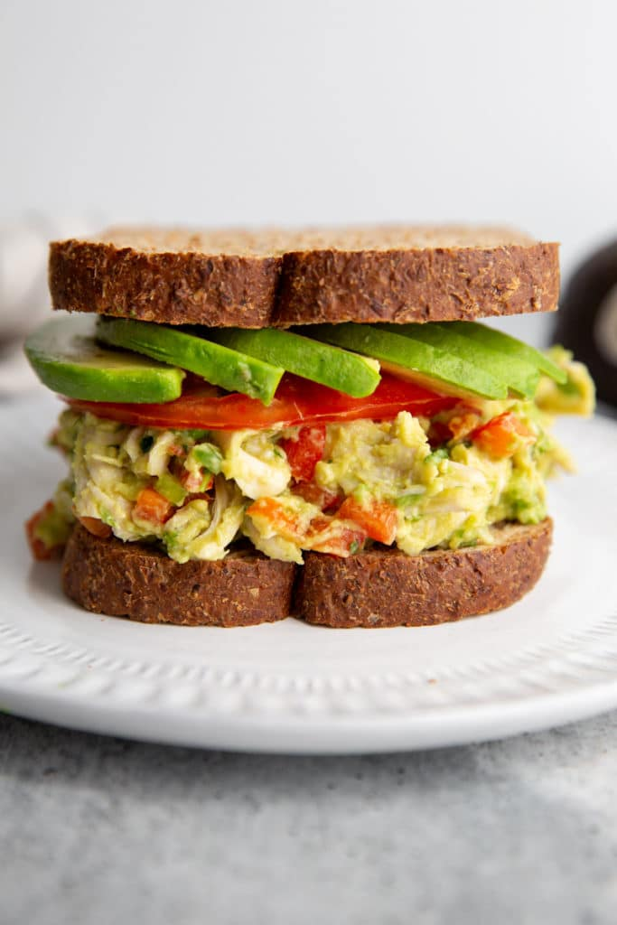 Avocado chicken salad in a sandwich with tomato and avocado slices.