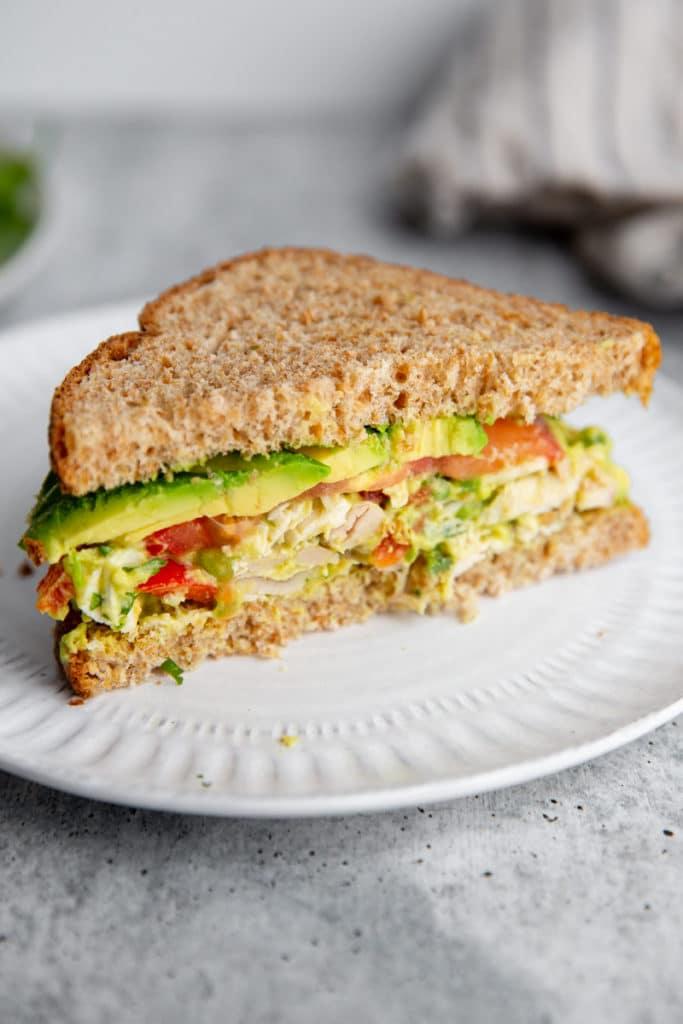 Half of a chicken salad sandwich on a plate.