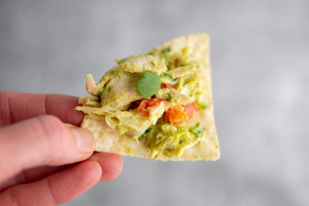 Hand holding a tortilla chip with avocado chicken salad on top.