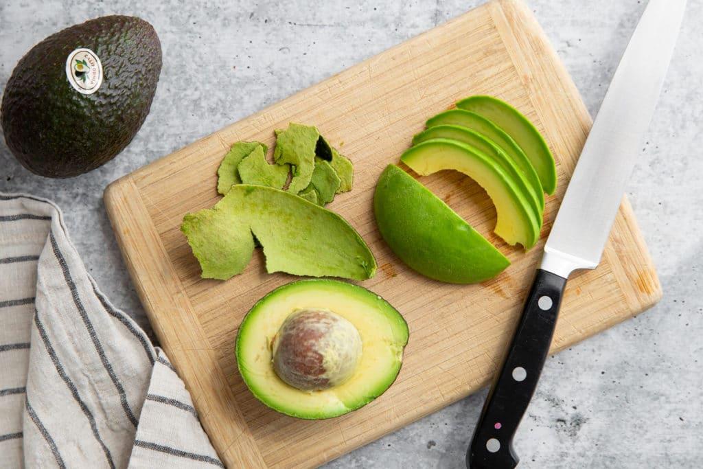 Avocado sliced on a cutting board.