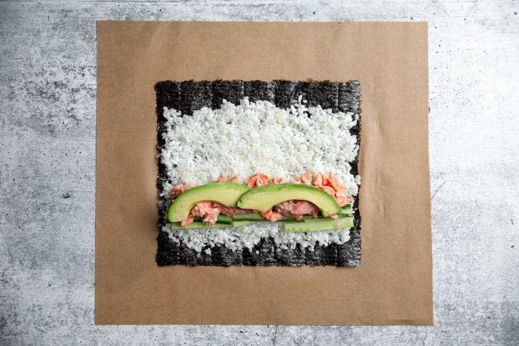 Nori on a piece of parchment paper topped with sushi rice, cucumber, salmon and avocado.