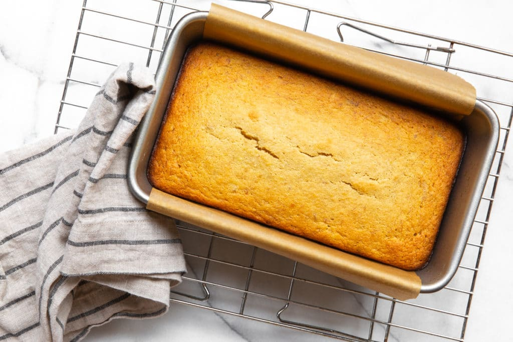 The baked banana bread in the pan on a cooling rack.
