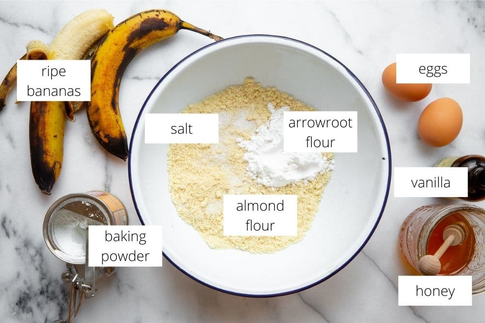 The ingredients for the gluten free banana bread recipe arranged on a marble surface with labels.
