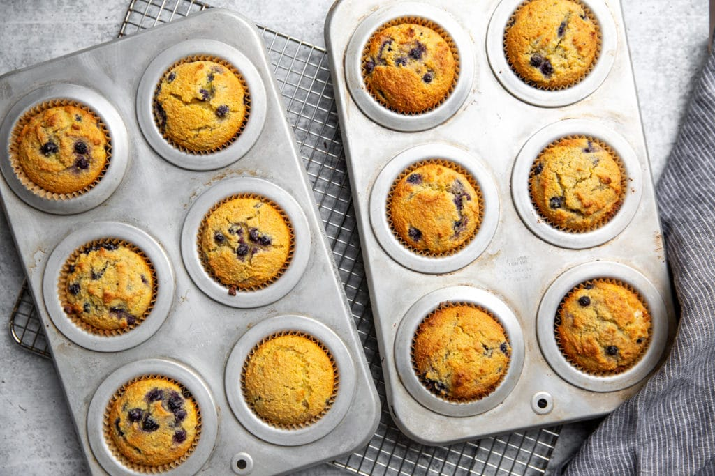 Baked blueberry corn muffins in muffin tins on a cooling rack.