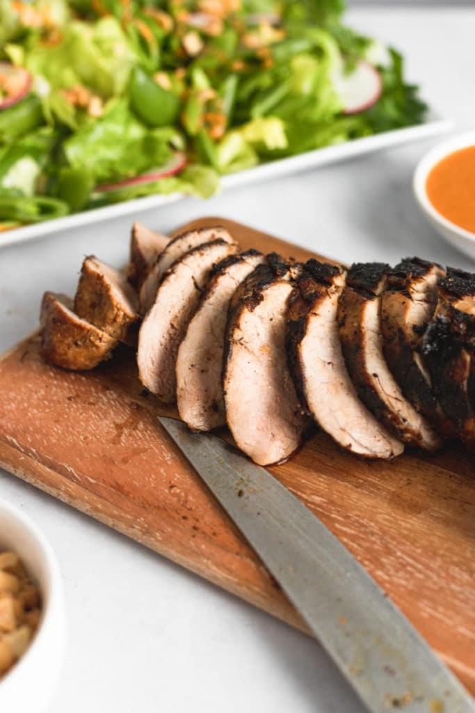 Grilled pork tenderloin sliced on a wooden cutting board.