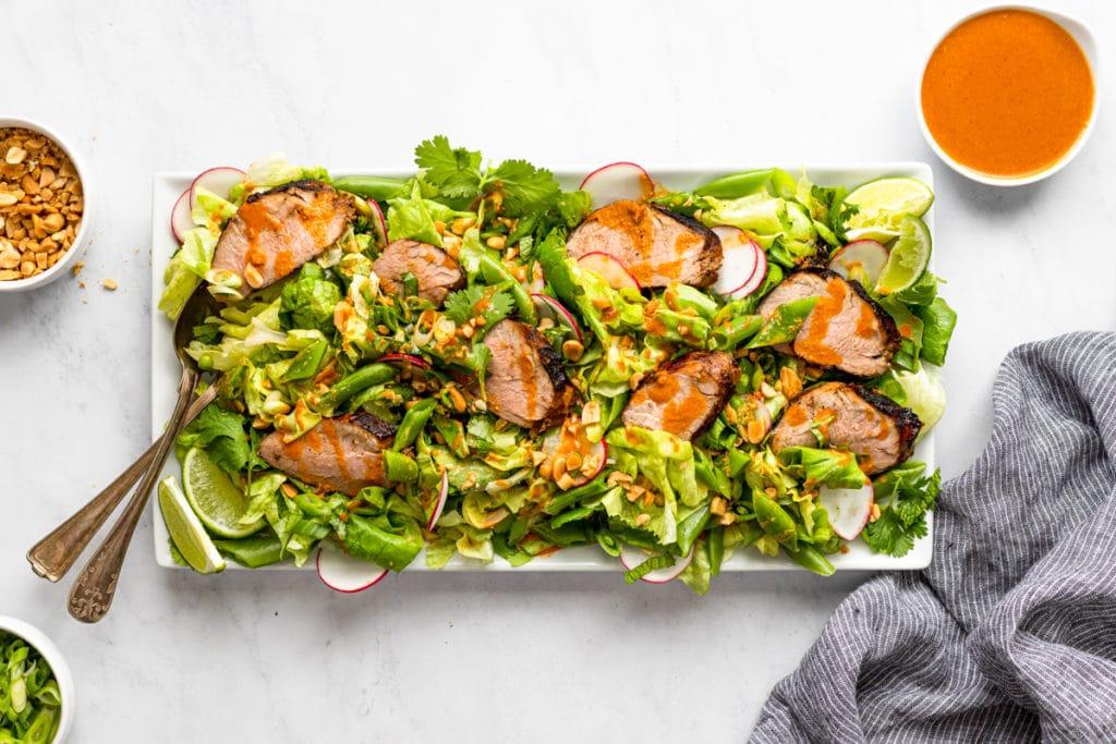Gochujang grilled pork tenderloin salad on a serving platter.