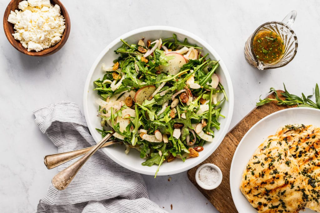 A bowl of baby potato, arugula and fennel salad, with grilled chicken alongside.