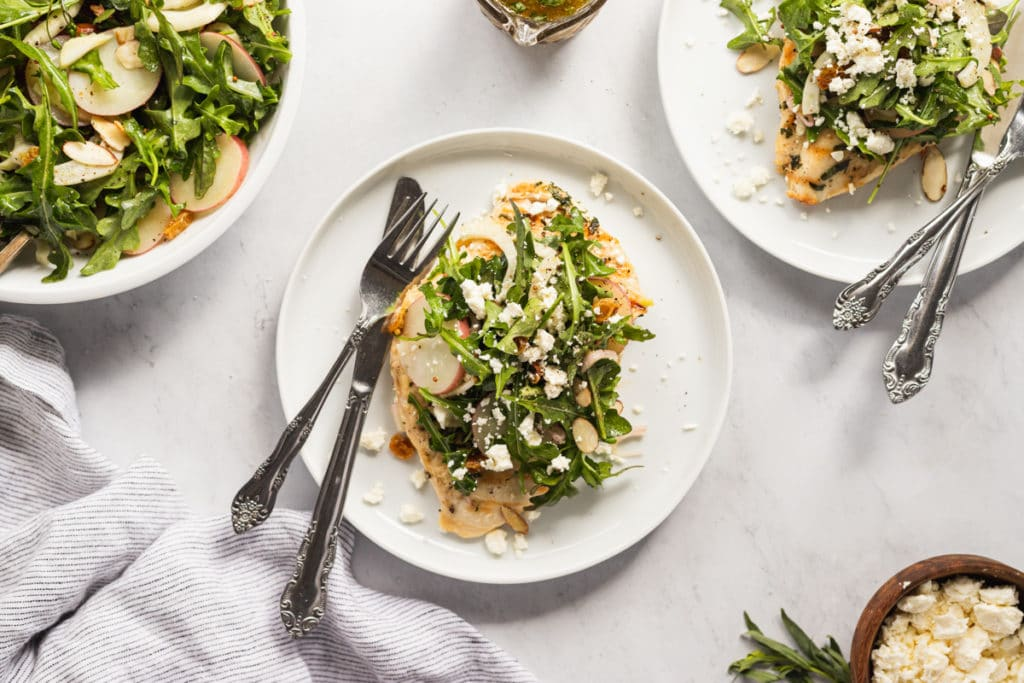 Overhead shot of chicken paillard on plates with arugula salad and dressing alongside.