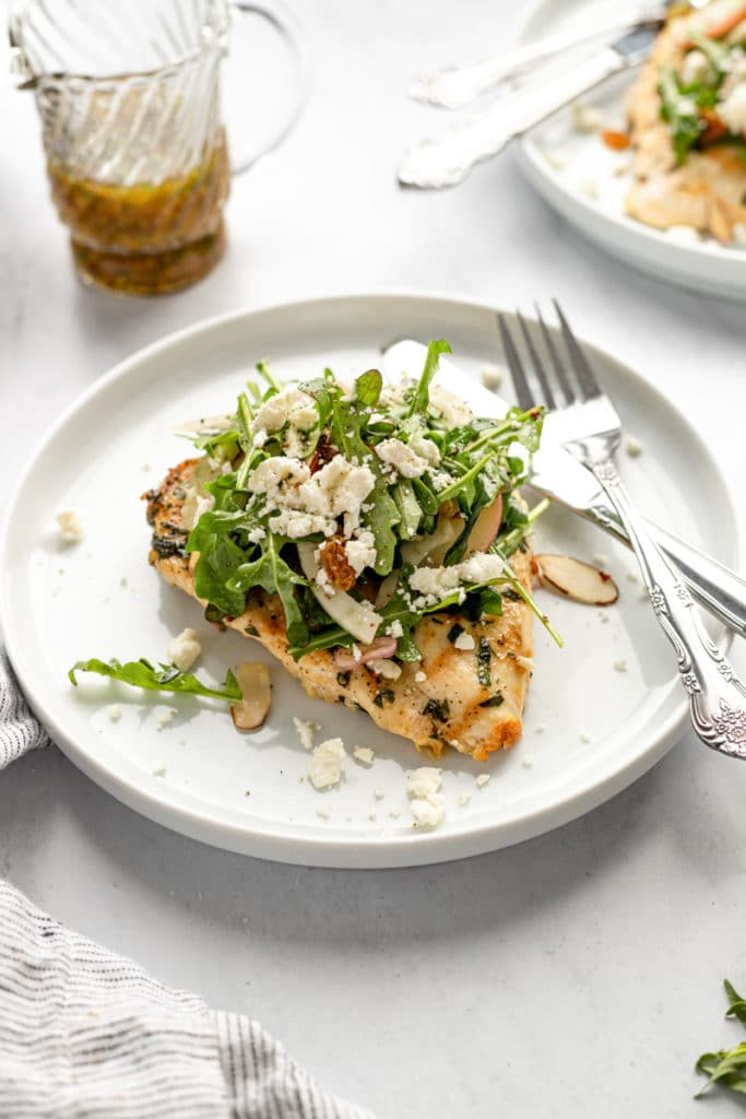Grilled chicken paillard on a plate, topped with arugula salad and feta.