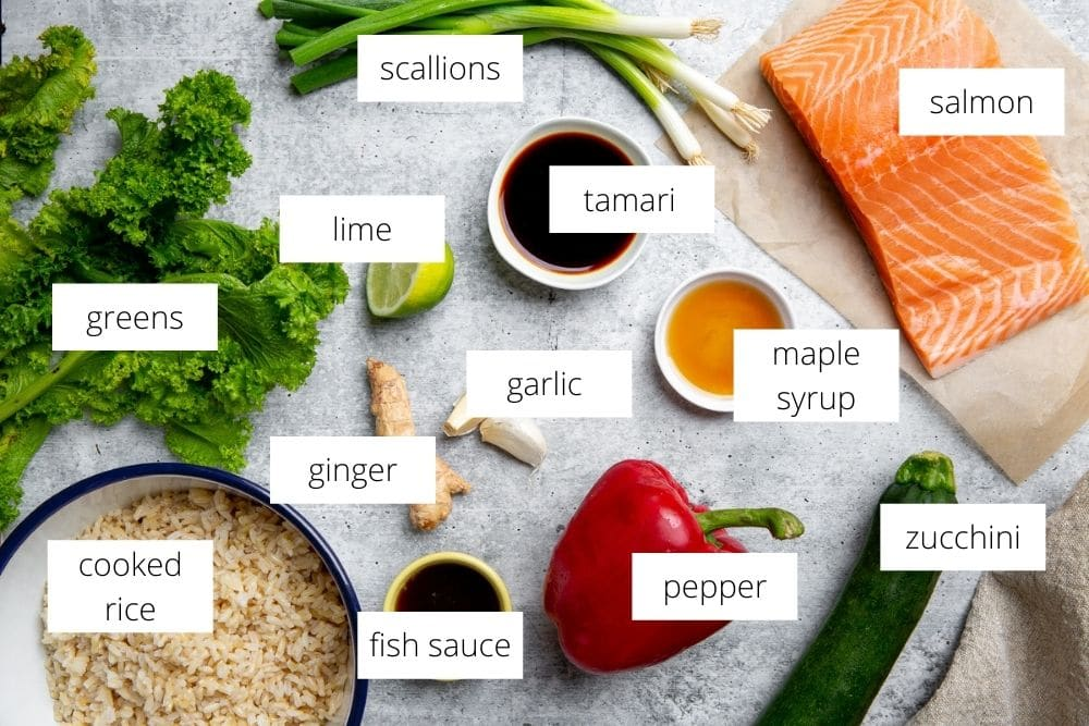 All of the ingredients for the salmon fried rice recipe arranged on a work surface and labeled.