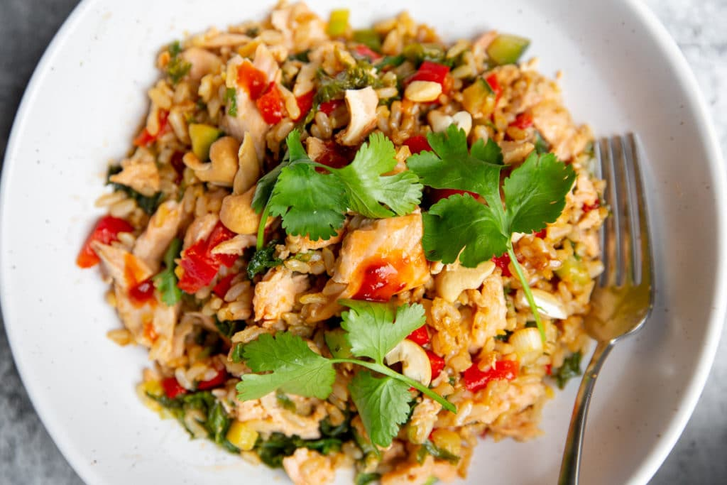 Salmon fried rice in a bowl, drizzled with chili sauce and topped with cilantro sprigs.