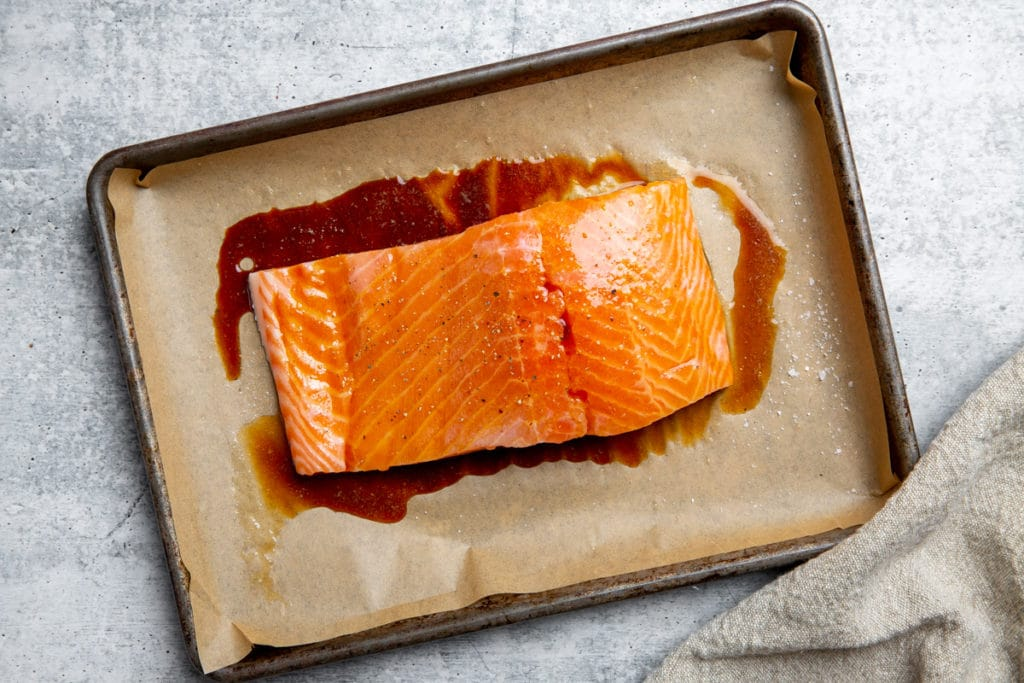 Salmon on a baking sheet drizzled with tamari.