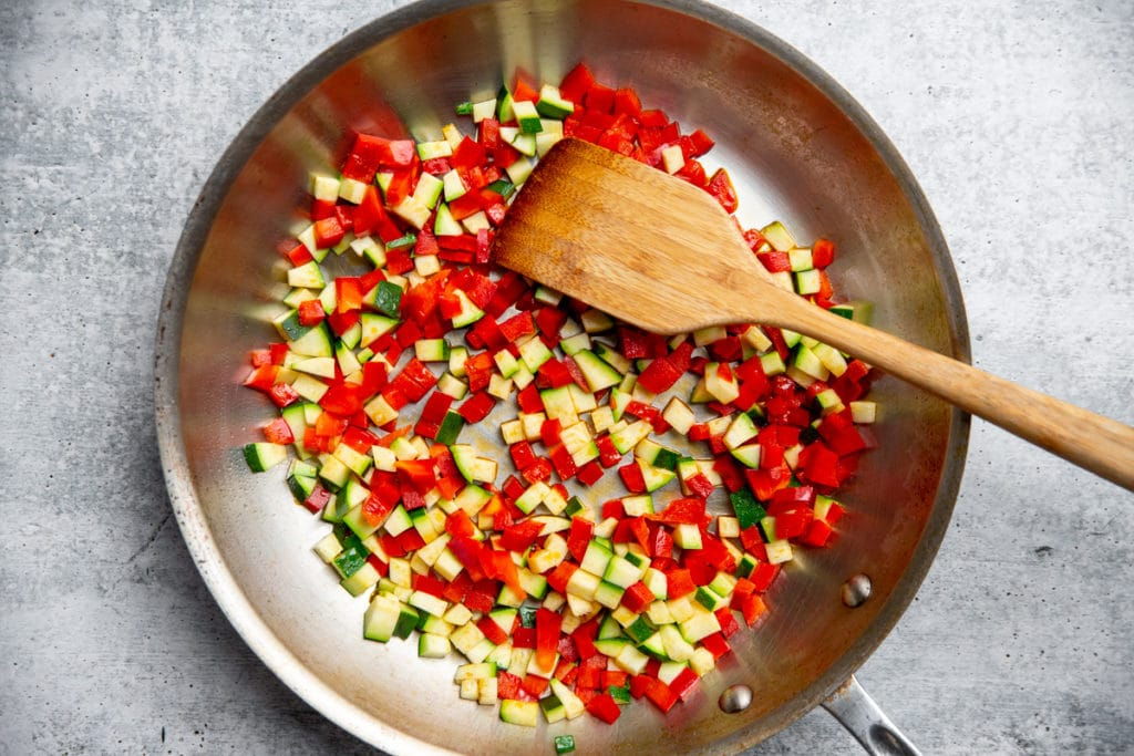 Process shot showing pepper and zucchini cooking in a large skillet.