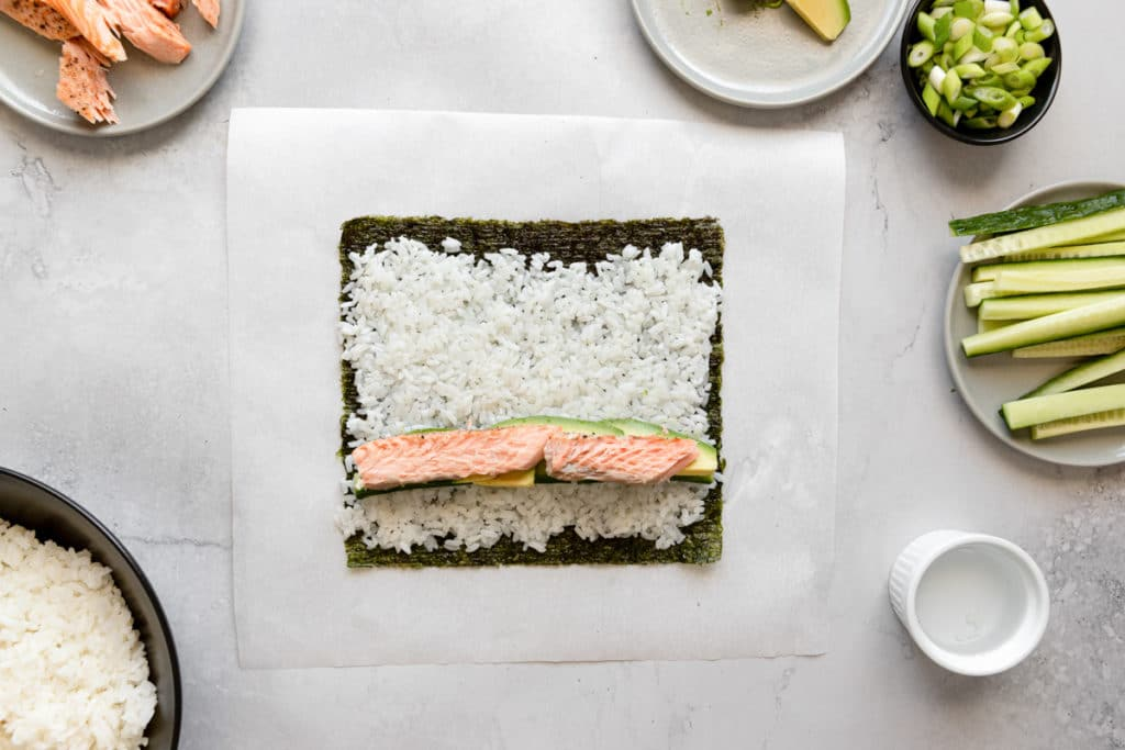 Process shot showing nori topped with sushi rice, avocado and cooked salmon.