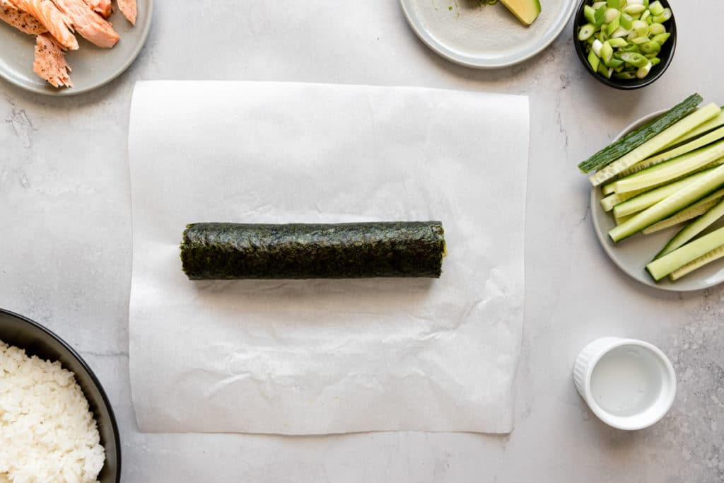 A rolled sushi roll on a piece of parchment paper.