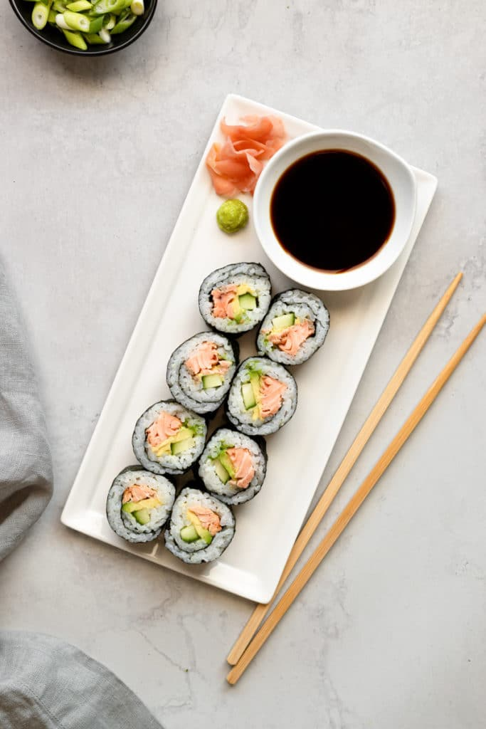 Salmon sushi rolls on a plate with chopsticks and soy sauce alongside.