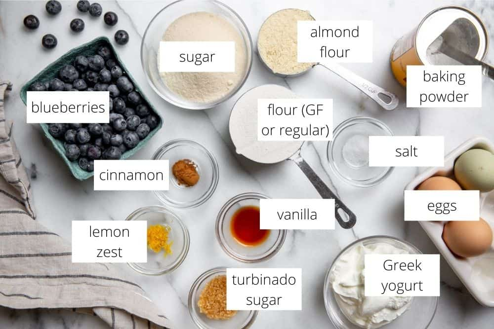 All of the ingredients for the blueberry cake recipe on a marble surface with labels.