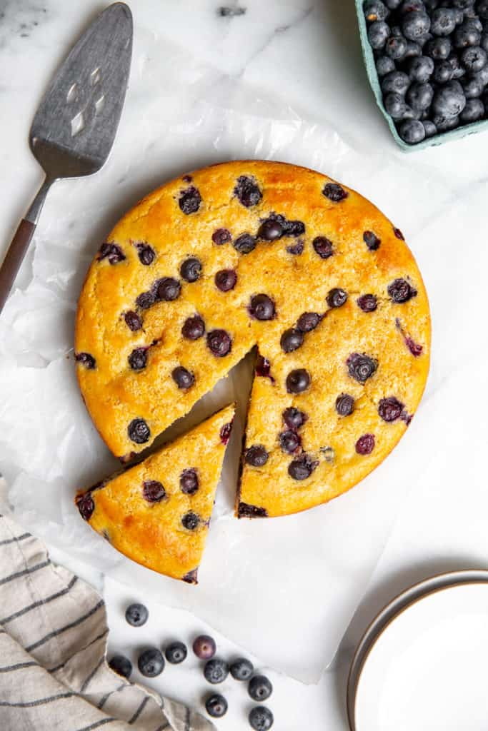 Blueberry yogurt cake on a marble surface with a slice cut out.