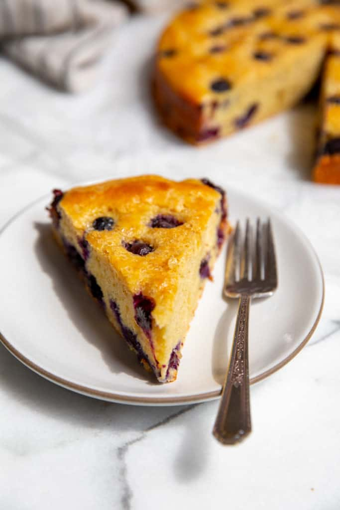 A slice of blueberry cake on a plate with a fork.