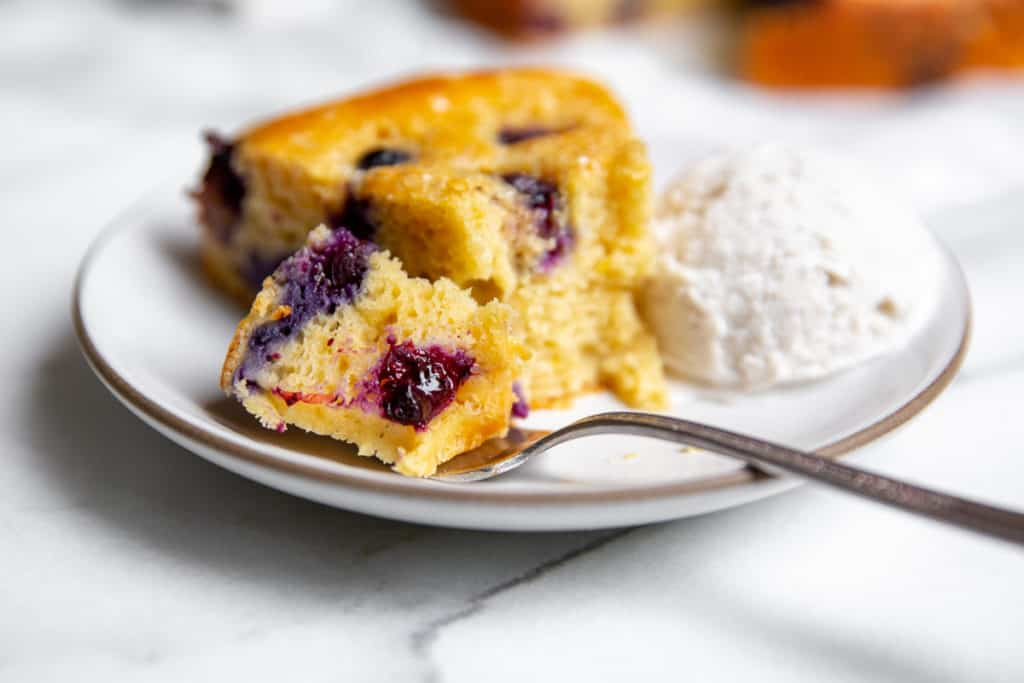 A bite of blueberry yogurt cake on a fork, with a slice of cake and scoop of ice cream in the background.