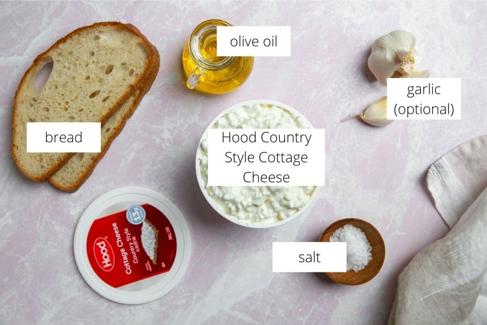 The ingredients for cottage cheese toasts arranged on a surface and labeled.