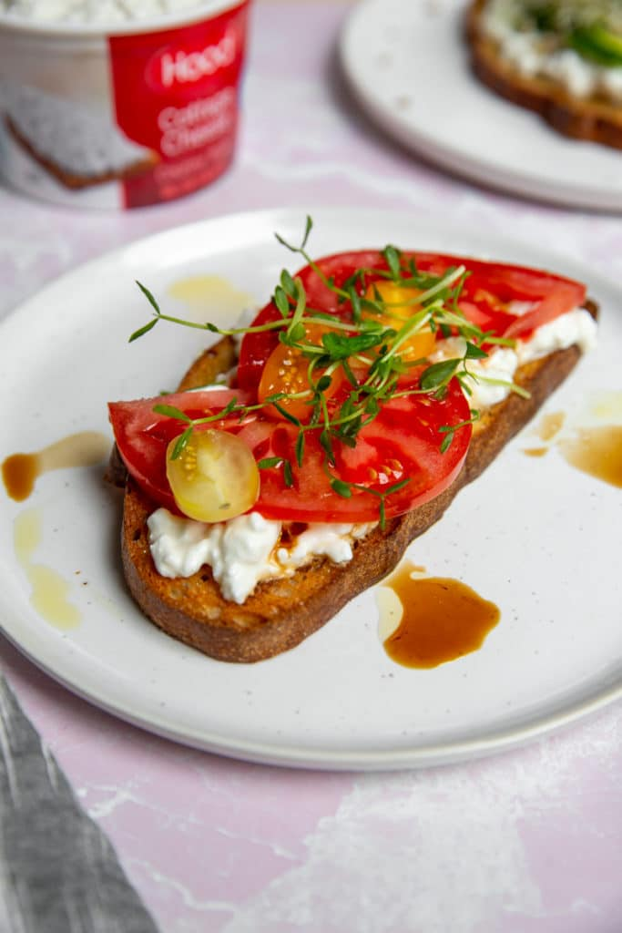 Close up of an open faced tartine topped with cottage cheese, tomatoes and sprouts.