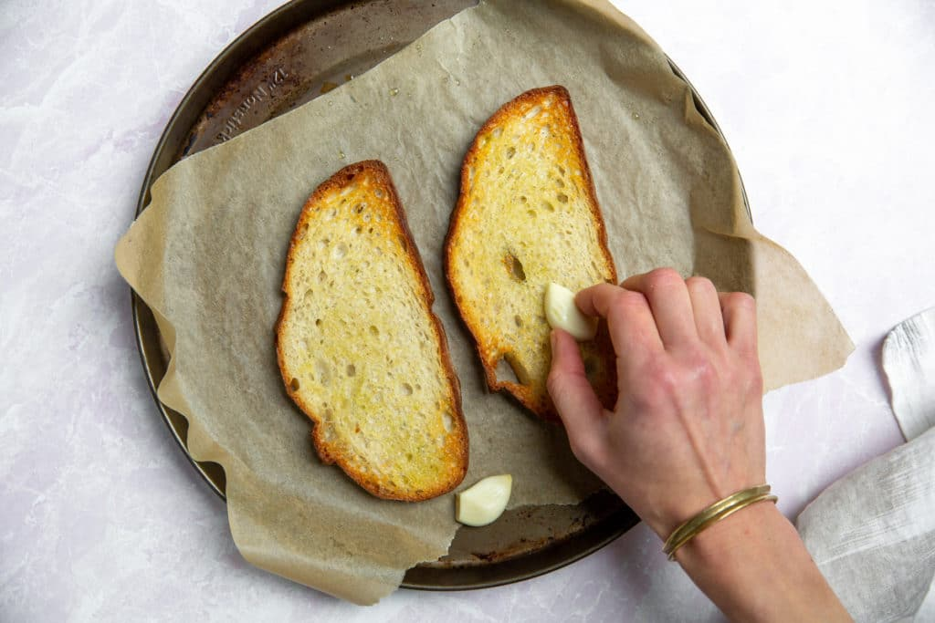 Process shot showing a hand rubbing warm toast with a halved garlic clove.