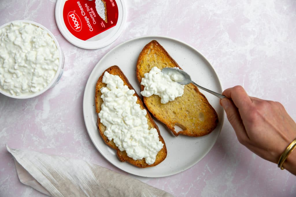 Process shot showing a hand spooning cottage cheese onto toasts.