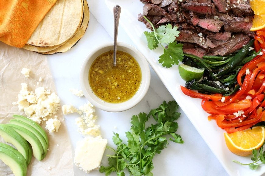 Grilled skirt steak and peppers on a platter, with a bowl of mojo sauce, crumbled cotija cheese, avocado slices and tortillas.
