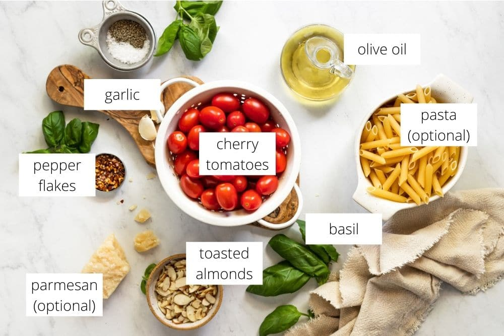All of the ingredients for the tomato pesto recipe arranged on a marble surface and labeled.