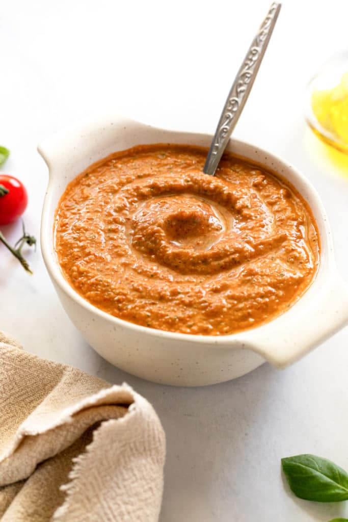 Red pesto in a bowl with a spoon.
