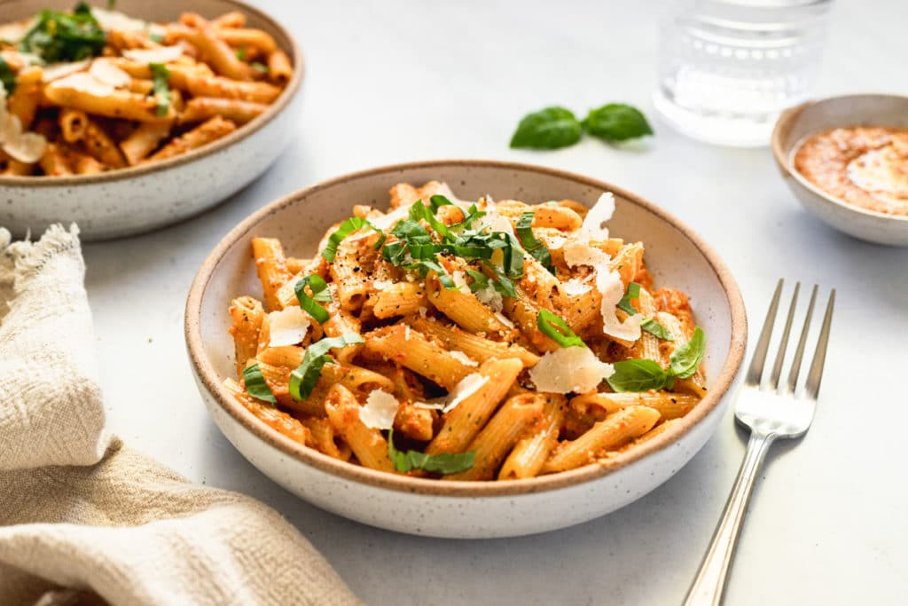 Tomato pesto tossed with penne pasta in a bowl with fresh basil and parmesan cheese.