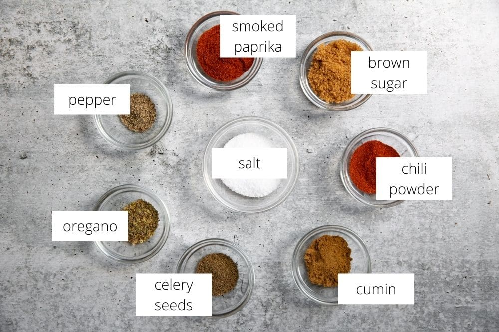 The pork butt spice rub ingredients in small bowls on a gray surface, with labels.
