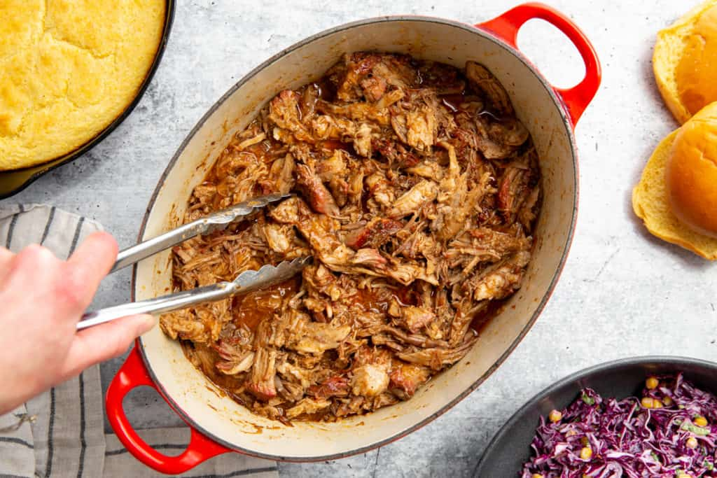 A hand grabbing smoked pulled pork from a pot using tongs.