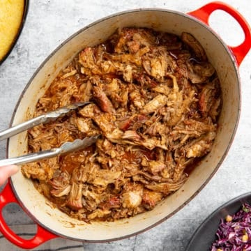 Traeger pulled pork in a pot with tongs.