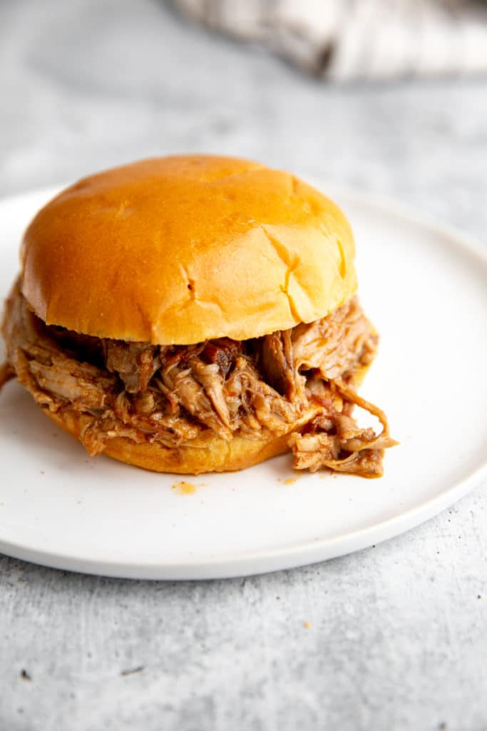 Pulled pork in a bun on a plate.