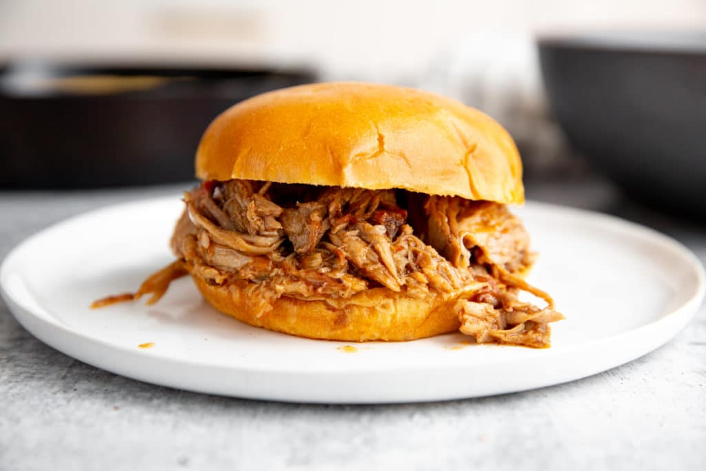 Smoked pulled pork in a bun on a plate.