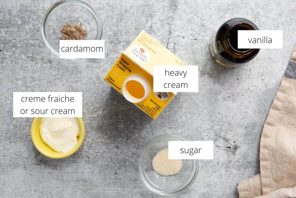 All of the ingredients for the cardamom whipped cream on a work surface, with labels.