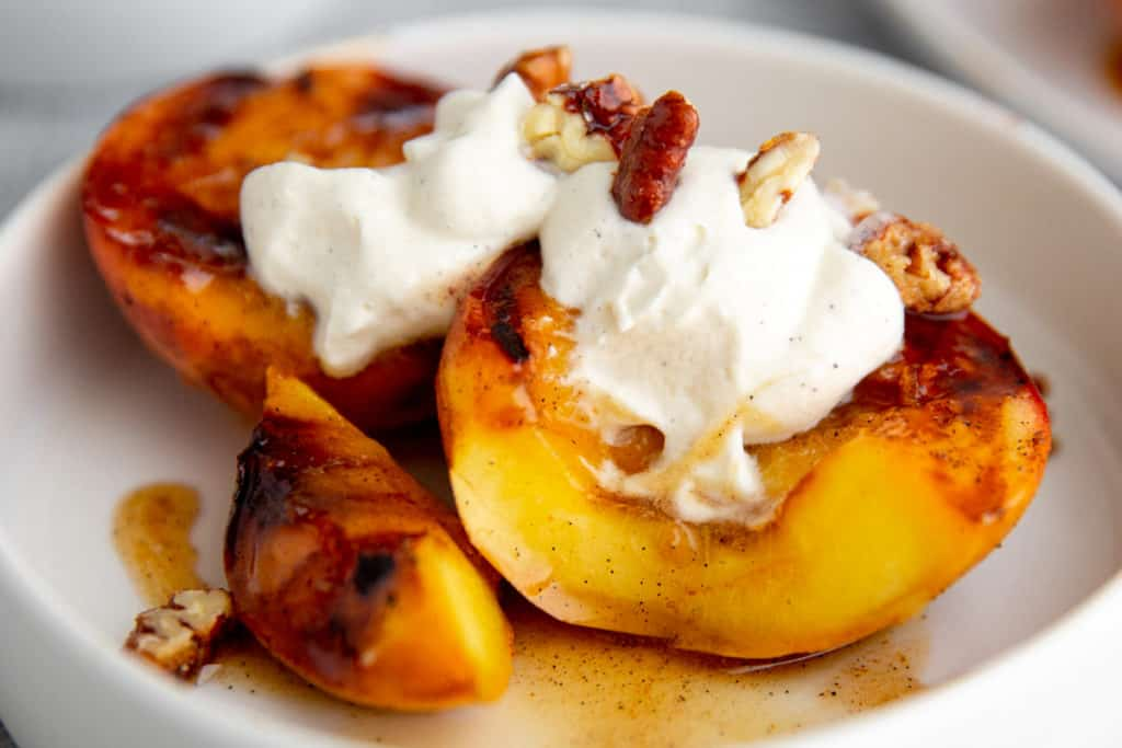 Grilled peaches topped with cardamom whipped cream.
