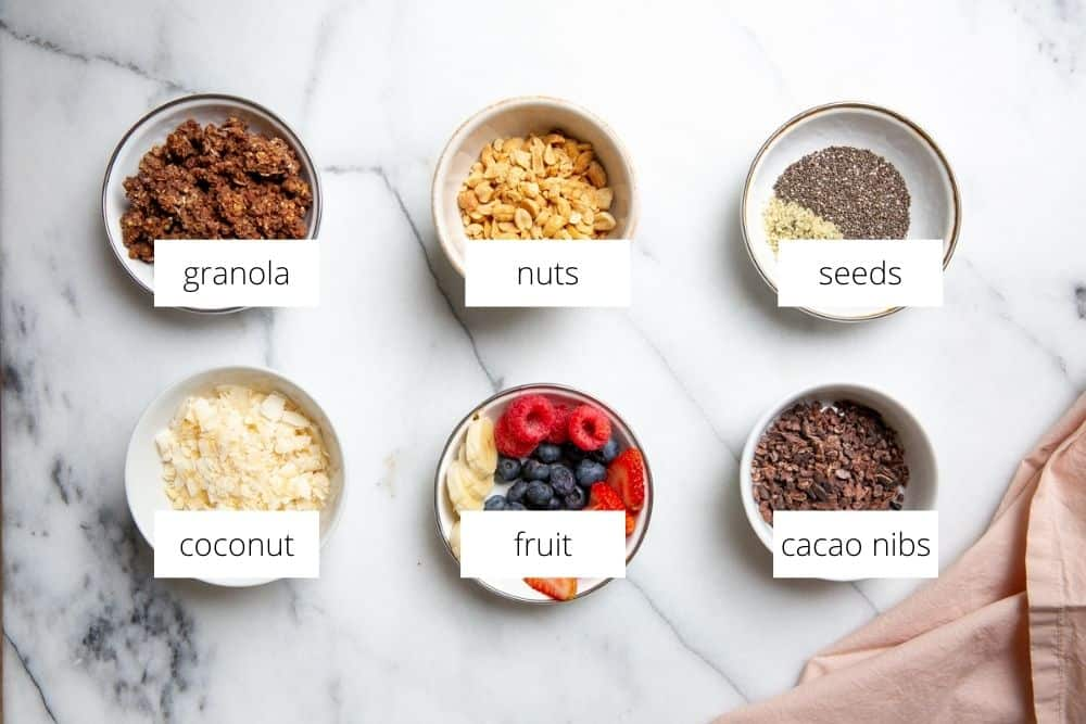 Smoothie bowl topping ideas arranged in bowls on a marble surface.