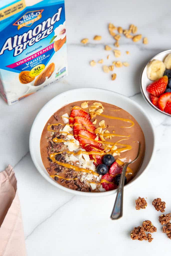 Chocolate smoothie bowl with a spoon, with a container of almond milk in the background.
