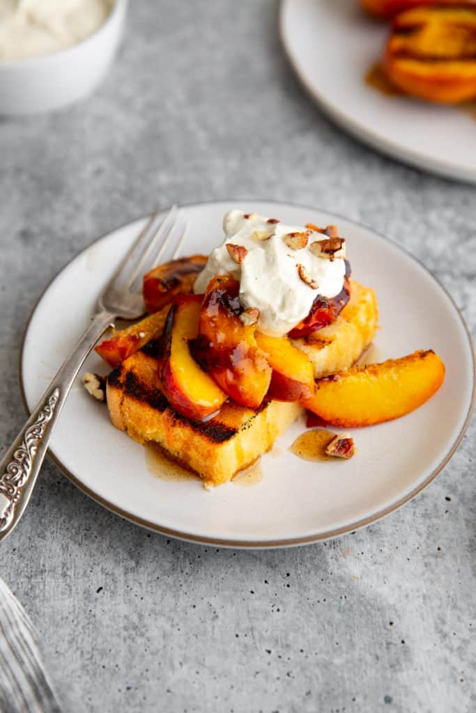 Peach shortcake featuring grilled peaches, grilled pound cake and whipped cream.
