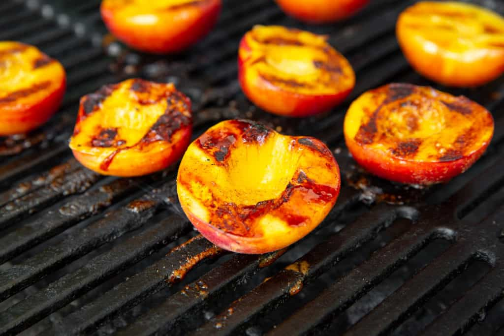 Close-up of grilled peaches on grill grates.